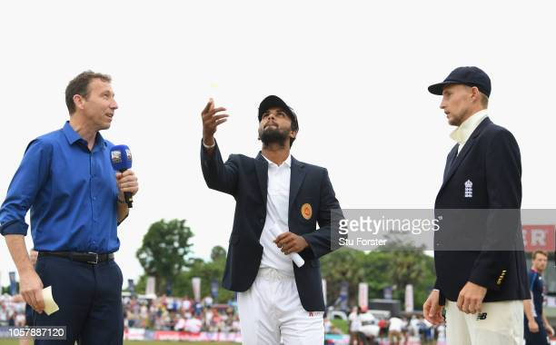 Sky presenter Michael Atherton looks on as Sri Lanka captain Dinesh Chandimal tosses the coin watched by Joe Root during Day One of the First Test...