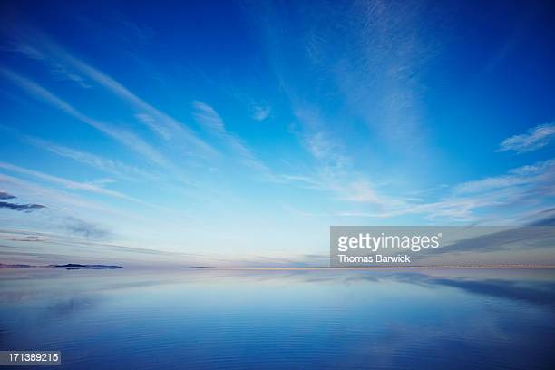 sky reflecting in calm lake at sunset - sunset lake stock photos and pictures