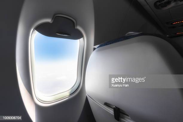 sky seen through airplane window - vehicle interior stock pictures, royalty-free photos & images