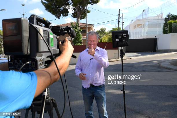 Sky Sports' British reporter Gary Coterill gestures as he works outside Barcelona's Argentinian forward Lionel Messi's house in Barcelona on August 3...