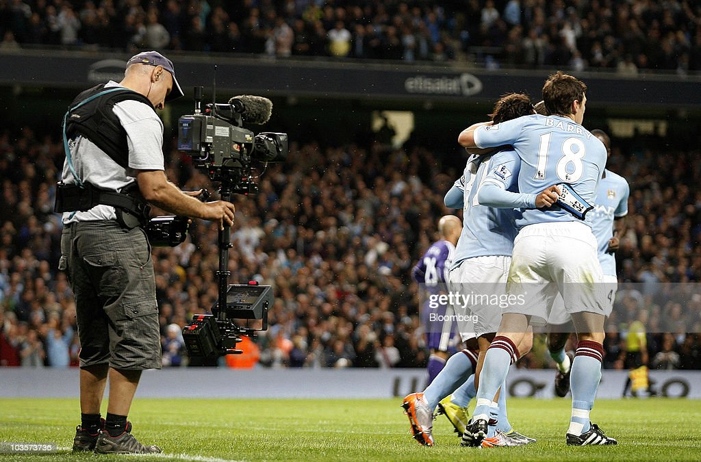A Sky Sports camera operator, left, films during Sky's television coverage of the soccer match between Manchester City and Liverpool, at the City of Manchester stadium in Manchester, U.K., on Monday, Aug. 23, 2010. British Sky Broadcasting Group Plc, which rejected News Corp.'s proposed bid for full ownership last month, said annual adjusted operating profit rose 10 percent as more clients signed up for high-definition television service. Photographer: Simon Bellis/Bloomberg via Getty Images