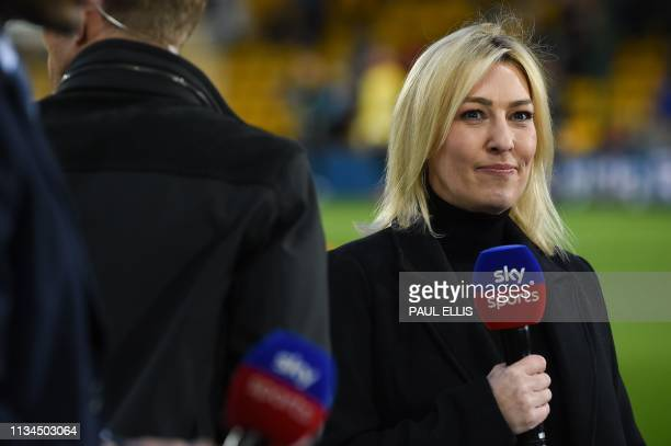 Sky Sports television presenter Kelly Cates holds is seen pitchside before kick off of the English Premier League football match between...