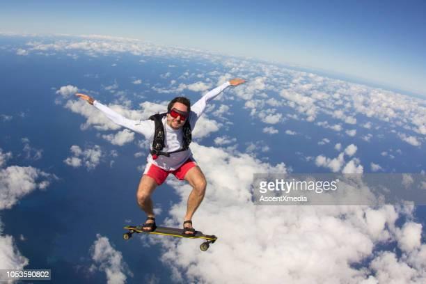 sky surfer falls with longboard through lofty skies - posizione descrittiva foto e immagini stock