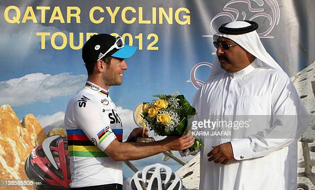 Sky Team rider Mark Cavendish of Great Britain receives his trophy and flowers from Sheikh Khaled bin Ali al-Thani, president of the Qatar Cycling...