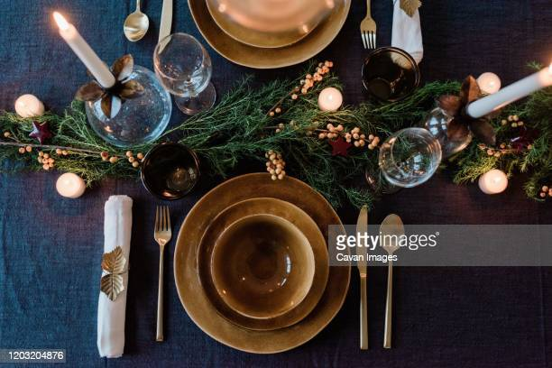 sky view of a modern dinner table setting with candles and greenery - eating utensil stock pictures, royalty-free photos & images