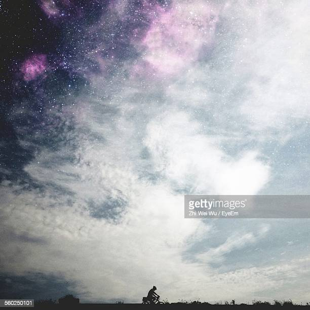 Sky With Clouds And Silhouette Of Biking Person