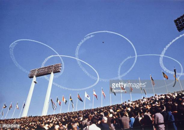 Sky writers trace the Olympic symbols interlocking rings in the air above the National stadium on Opening day