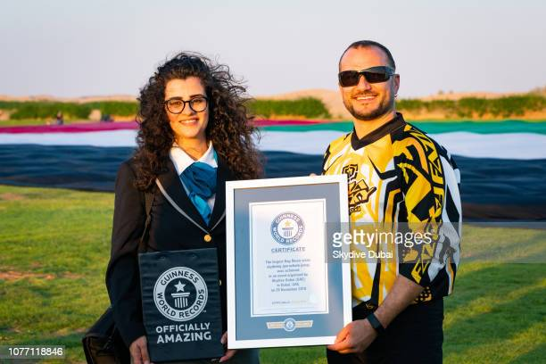 Skydive Dubai's David Junior Ludvik left receives an official plaque from a Guinness World Records representative on behalf of Skydive Dubai after...