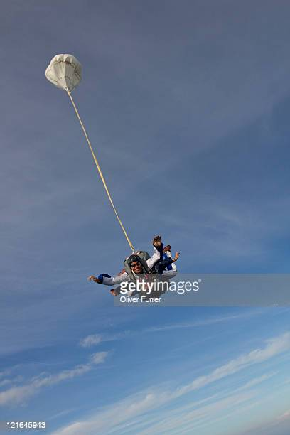A skydive tandem couple on the braking parachute.
