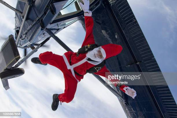 skydiver dressed as santa claus falls towards the earth - christmas plane stock pictures, royalty-free photos & images