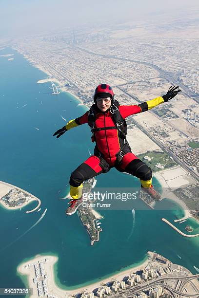 Skydiver girl flying high over Dubai beach