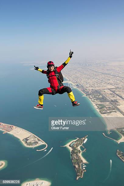 Skydiver girl flying high over the Dubai beach