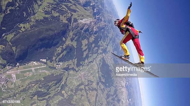 フリーフォールのスカイダイバー、mtnの上のスノーボードで - スカイダイビング ストックフォトと画像