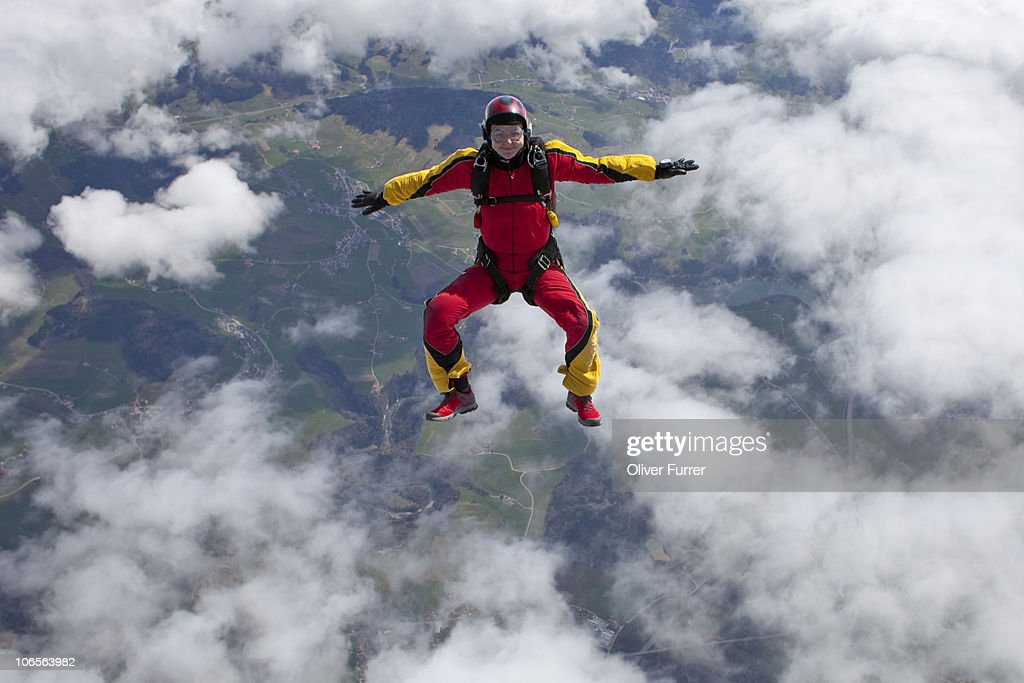 Skydiver is flying high in the sky over clouds.