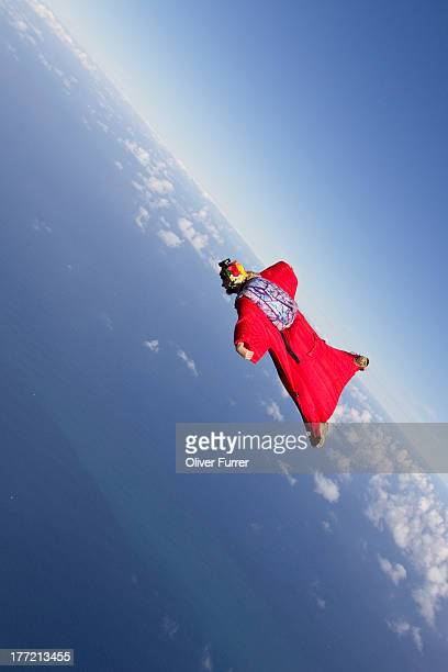 Skydiver is flying within a wingsuit over the sea