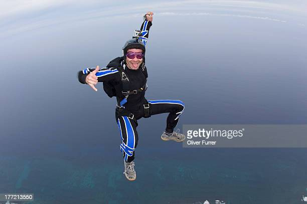 Skydiver is having fun in the sky over the sea