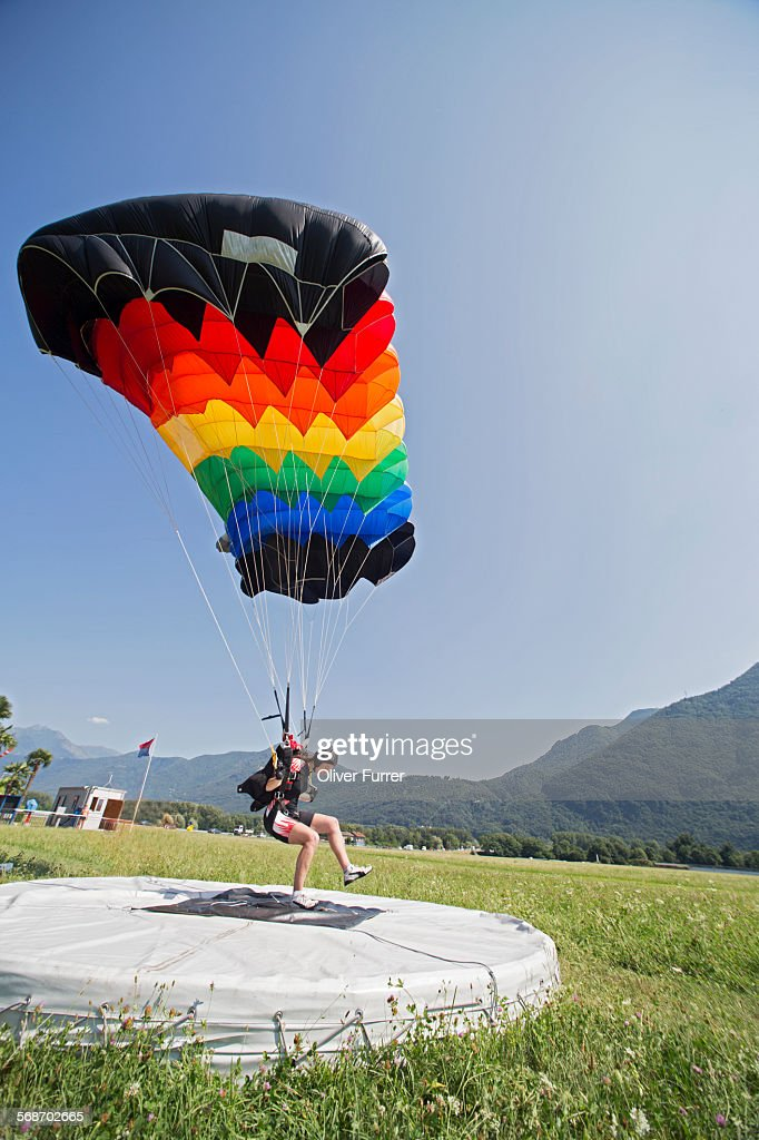 Skydiver is landing with the parachute on the spot : Stock Photo