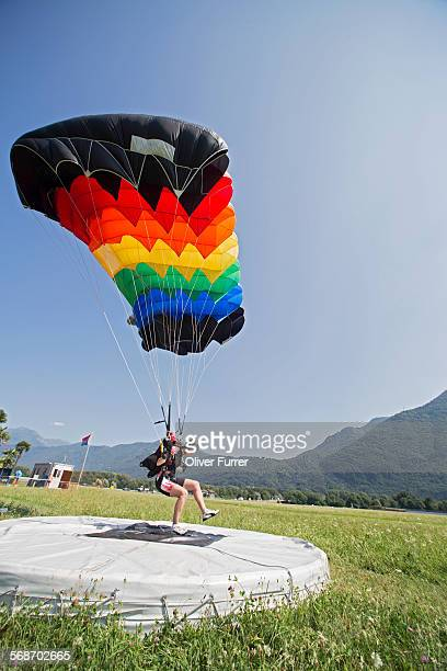 Skydiver is landing with the parachute on the spot