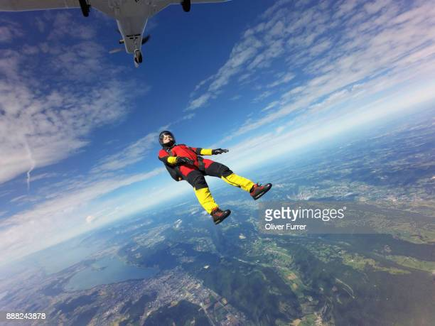 Skydiver jumped off an aircraft and is tracking backwards in a straight position high in the blue sky.