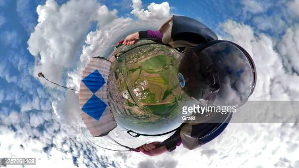 skydiver piloting his parachute with a 360 degree camera. - diving to the ground stock pictures, royalty-free photos & images