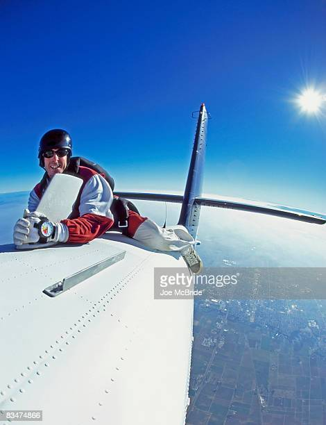 skydiver riding atop airplane in flight. - vertical stabilizer stock pictures, royalty-free photos & images