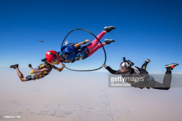A skydiver sails through a hula hoop while two other licensed skydivers hold the hoop secure during freefall The freefall fun took place during...