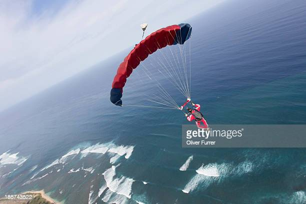 Skydiver with red parachute above Honolulu,  Hawaii