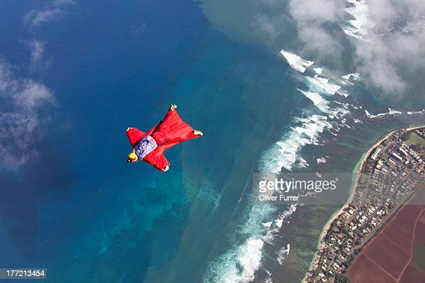 Skydiver with wingsuit is flying over the sea