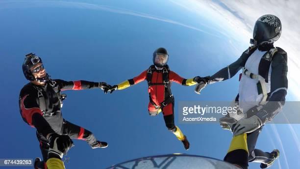 Skydivers create formation above rural landscape
