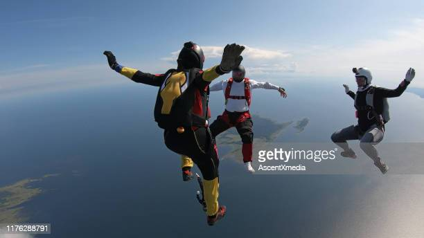 skydivers fall through clear skies, in aerial flight - gliding stock pictures, royalty-free photos & images