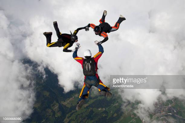 skydivers fall towards the earth - tre persone foto e immagini stock