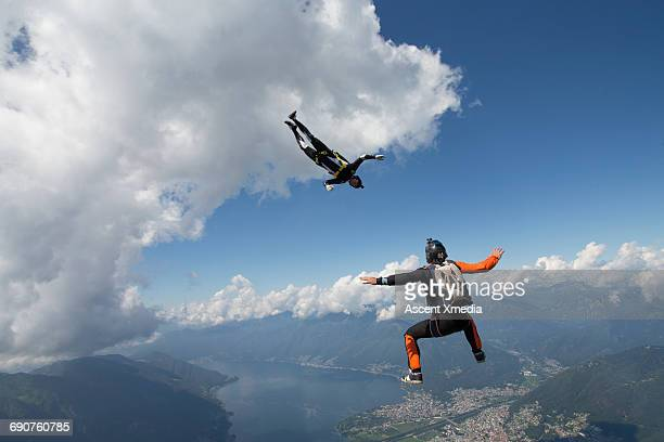 Skydivers in freefall above mountains, lake