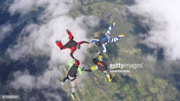 pov of skydivers in freefall, over rural landscape - four people stock pictures, royalty-free photos & images