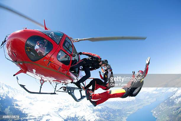 Skydivers jumping out of a helicopter