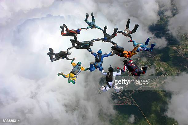 skydivers make a formation above the clouds - partnership stock pictures, royalty-free photos & images