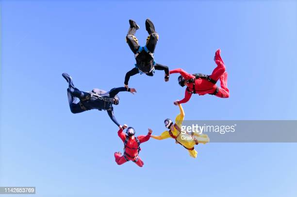skydivers making a star shape - jumpsuit stock pictures, royalty-free photos & images
