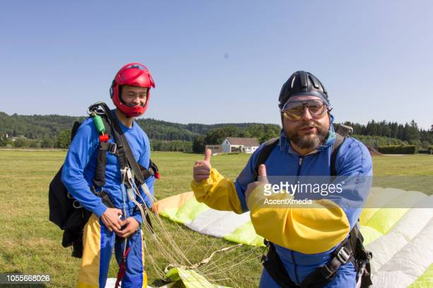 skydivers smile at camera after landing - only mid adult men stock pictures, royalty-free photos & images