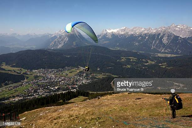 Skydivers taking off near Mittelstation Rosshutte with Seefeld town in background.