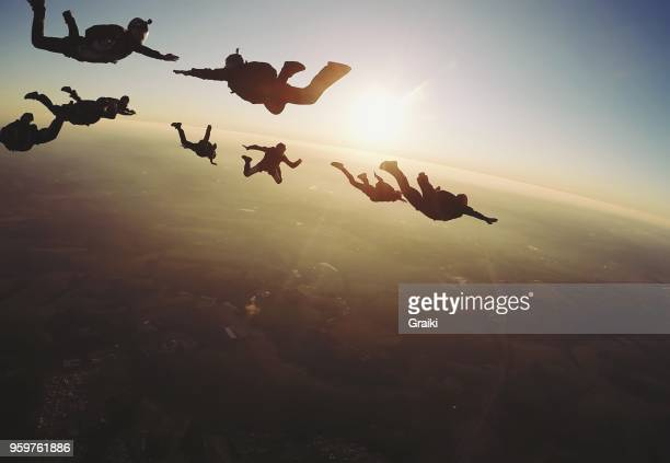 skydiving group at the sunset - sports team event stock photos and pictures