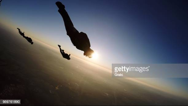 skydiving group at the sunset - impressionante foto e immagini stock