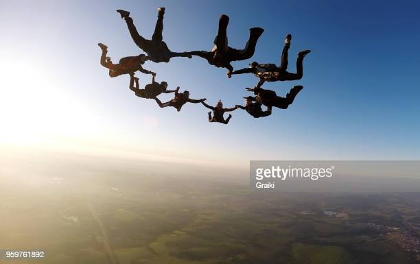 skydiving group at the sunset - sportteam stockfoto's en -beelden