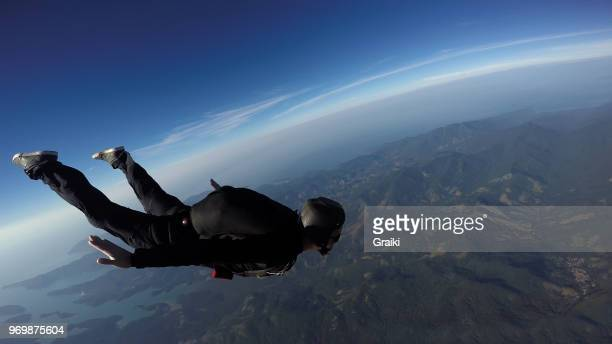 skydiving man jumping over the sea at a sunrise - ヘッドスライディング ストックフォトと画像