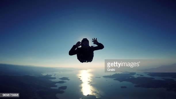 Skydiving man jumping over the sea at a sunrise