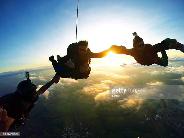 Skydiving tandem holding hands at the sunset