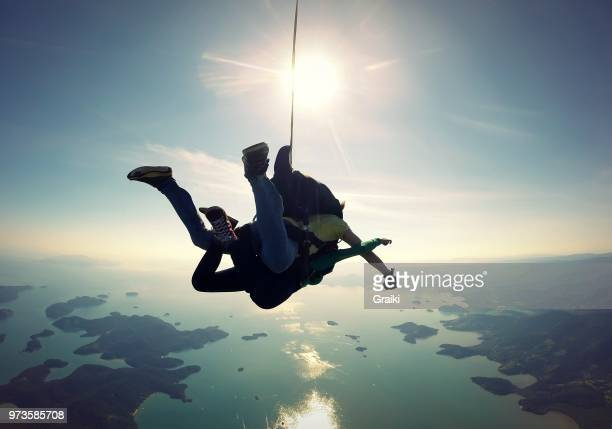 skydiving tandem over the sea - fallschirm stock-fotos und bilder