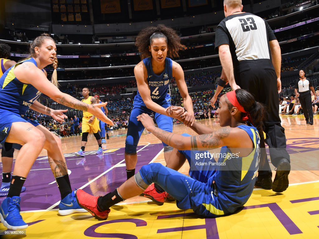 Skylar Diggins-Smith #4 of the Dallas Wings helps up teammage Glory Johnson #25 during the game against the Los Angeles Sparks on July 12, 2018 at STAPLES Center in Los Angeles, California.