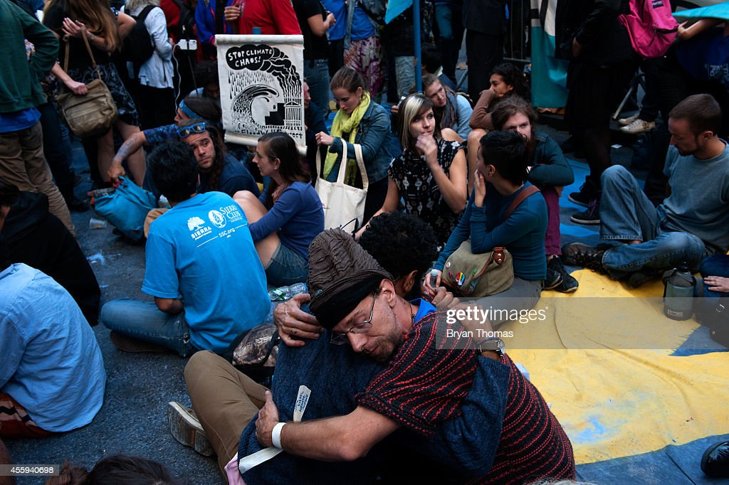 Skylar Dunn-Lubin (L) and Eco Lake (R) hug in the middle of Broadway during the Flood Wall Street protest on September 22, 2014 in New York City. The Flood Wall Street protest came on the heels of the climate change march on September 21 that attracted over 300,000 protestors.