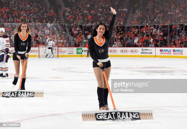 Skylar Grace and Kristen Mee of the Philadelphia Flyers ice girls clean the ice during a timeout against the Edmonton Oilers on October 21 2017 at...