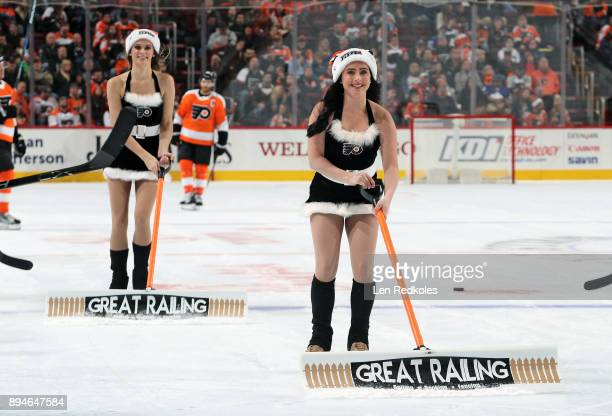 Skylar Grace and Kristen Mee of the Philadelphia Flyers ice girls clean the ice during a timeout against the Toronto Maple Leafs on December 12 2017...
