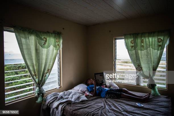Skyler Hopkins of Barbuda lays on the bed of his room as he reads a book at home on November 29 in Codrington Antigua and Barbuda Hopkins' family...